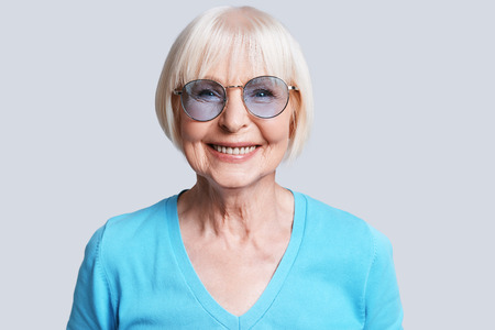Trendy senior female. Beautiful senior woman looking at camera and smiling while standing against grey background