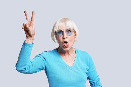 Crazy lady. Playful senior woman making peace sign and making a face while standing against grey background