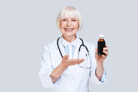 Recommended medicines. Beautiful senior woman in lab coat holding a bottle with medicines and smiling while standing against grey background