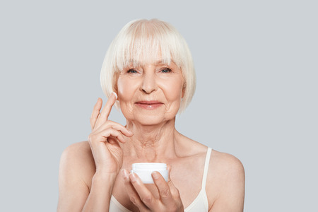 Anti aging. Beautiful senior woman applying beauty product while standing against grey background Stock Photo