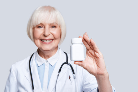 New antibiotic. Beautiful senior woman in lab coat holding a bottle with medicines and smiling while standing against grey background
