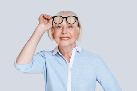 Always confident. Beautiful senior woman adjusting eyewear and smiling while standing against grey background Stock Photo