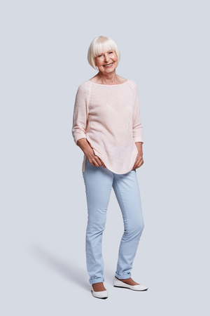 Just be happy! Full length of beautiful senior woman looking at camera and smiling while standing against grey background