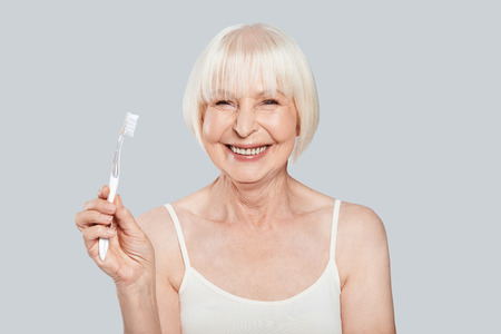 Dental health. Beautiful senior woman holding toothbrush and smiling while standing against grey background Stock Photo - 109476220