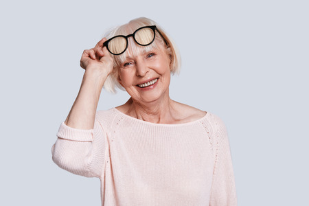 Perfect in every way. Beautiful senior woman adjusting eyewear and smiling while standing against grey background Stock Photo - 109476221