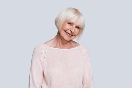 Feeling so happy! Beautiful senior woman looking at camera and smiling while standing against grey background