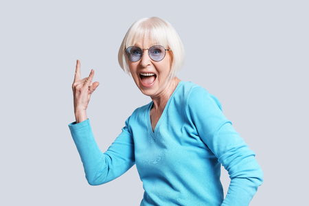 Rock it! Playful senior woman making rock on sign and smiling while standing against grey background