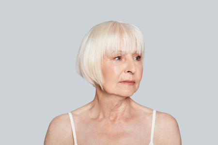 Totally calm. Beautiful senior woman looking away while standing against grey background Stock Photo