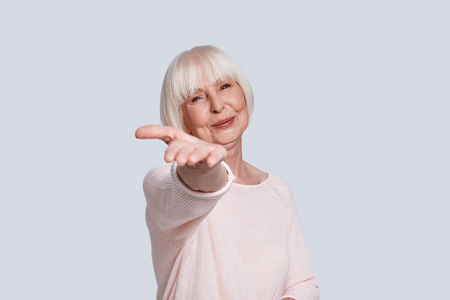 True happiness. Beautiful senior woman looking at camera and smiling while standing against grey background Stock Photo - 109476226