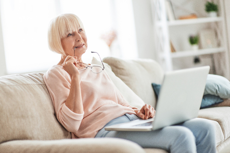 What if... Beautiful senior woman using laptop and thinking about something while relaxing on the couch at home