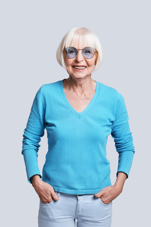 Always young inside. Beautiful senior woman looking at camera and smiling while standing against grey background
