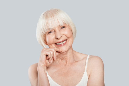 Sincere smile. Beautiful senior woman looking at camera and smiling while standing against grey background