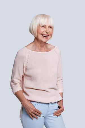 Just happiness. Beautiful senior woman looking away and smiling while standing against grey background Stock Photo