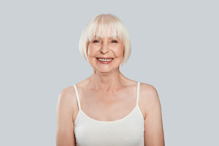Natural beauty. Beautiful senior woman looking at camera and smiling while standing against grey background Stock Photo
