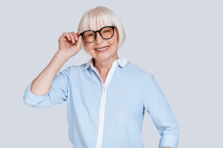 Modern businesswoman. Beautiful senior woman adjusting eyewear and smiling while standing against grey background