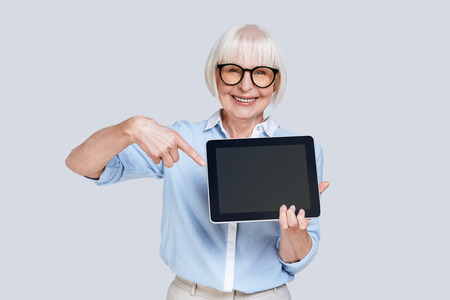 Take a look over here! Beautiful senior woman pointing at digital tablet and smiling while standing against grey background Stock Photo