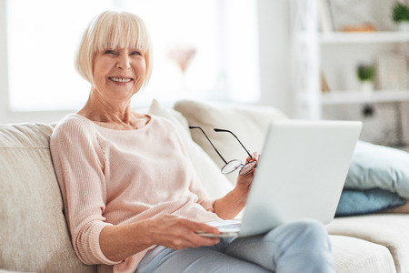 Surfing the net at home. Beautiful senior woman looking at camera and smiling while relaxing on the couch at home