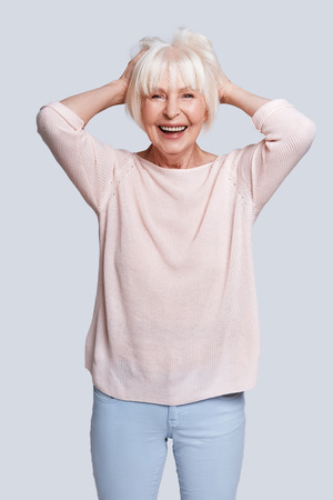 No cares. Beautiful senior woman keeping hands in hair and smiling while standing against grey background