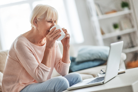 Pleasant memories. Beautiful senior woman drinking coffee while relaxing on the couch at home Stock Photo