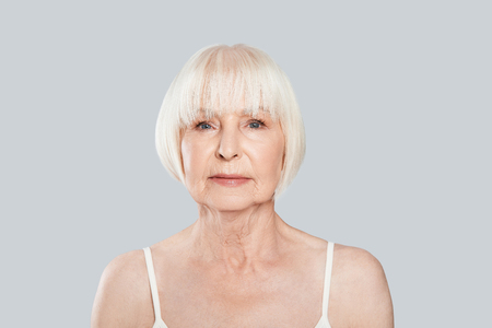 Human age. Beautiful senior woman looking at camera while standing against grey background