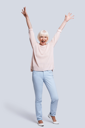 Yes! Full length of beautiful senior woman keeping arms raised and shouting while standing against grey background