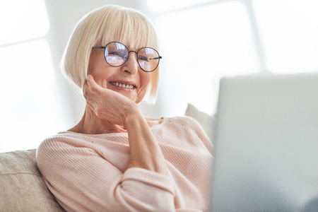Focusing on something. Beautiful senior woman using laptop and smiling while relaxing on the couch at home