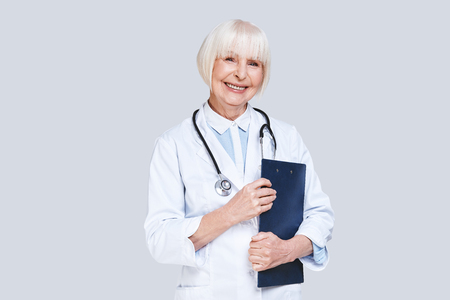 Taking good care of you. Beautiful senior woman in lab coat looking at camera and smiling while standing against grey background
