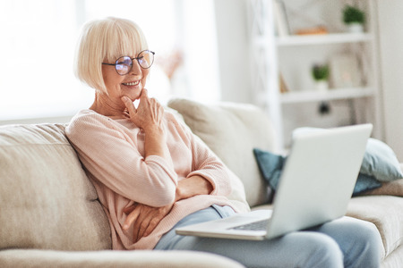 Resting at home. Beautiful senior woman using laptop and smiling while relaxing on the couch at home