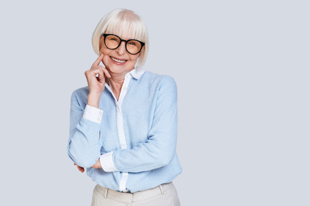 Experienced businesswoman. Beautiful senior woman looking at camera and smiling while standing against grey background Stock Photo