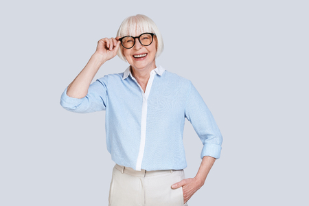 Time to do business. Beautiful senior woman adjusting eyewear and smiling while standing against grey background Stock Photo
