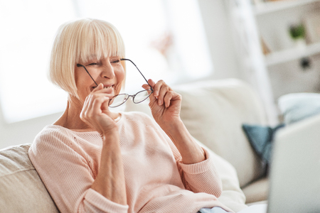 Happy granny. Beautiful senior woman putting on her eyewear while relaxing on the couch at home Stock Photo