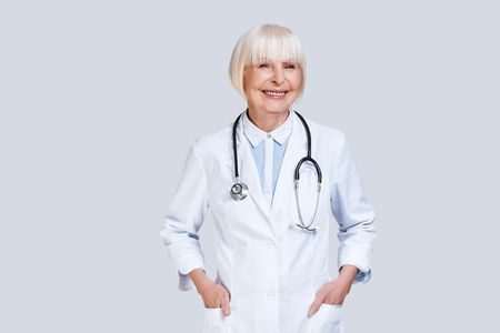 Healthcare worker. Beautiful senior woman in lab coat looking at camera and smiling while standing against grey background Stock Photo