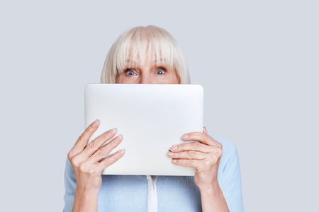 Feeling playful. Beautiful senior woman covering face using digital tablet while standing against grey background Stock Photo