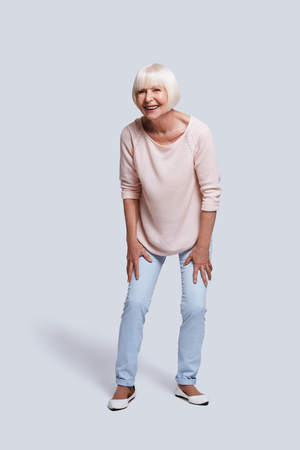 Carefree. Full length of beautiful senior woman looking away and smiling while standing against grey background