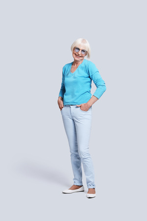 Trendy grandmother. Full length of beautiful senior woman looking at camera and smiling while standing against grey background Stock Photo