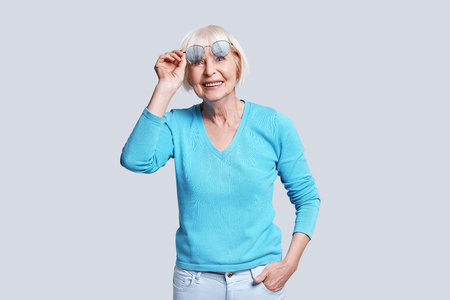 Trendy look. Beautiful senior woman adjusting eyewear and smiling while standing against grey background Stock Photo