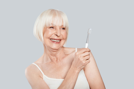 Taking good care of teeth. Beautiful senior woman holding toothbrush and smiling while standing against grey background Stock Photo - 109475974