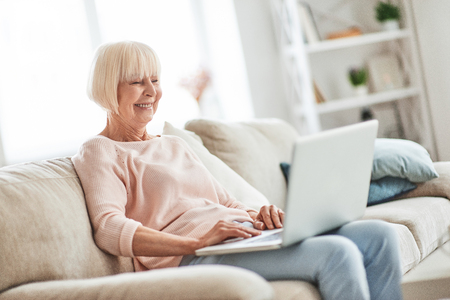 Using modern technologies. Beautiful senior woman using laptop and smiling while relaxing on the couch at home
