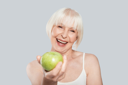Would you like some? Beautiful senior woman holding an apple and smiling while standing against grey background