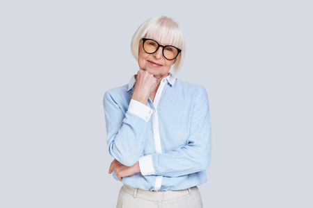 Retirement is a fresh start. Beautiful senior woman looking at camera and smiling while standing against grey background