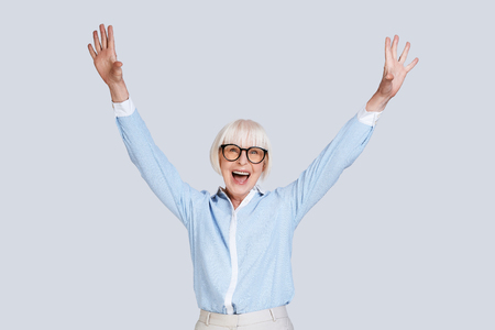 Victory! Beautiful senior woman gesturing and smiling while standing against grey background