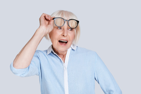Unbelievable. Surprised senior woman adjusting eyewear and making a face while standing against grey background