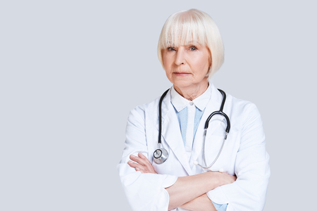 General practitioner. Beautiful senior woman in lab coat looking at camera and keeping arms crossed while standing against grey background Stock Photo