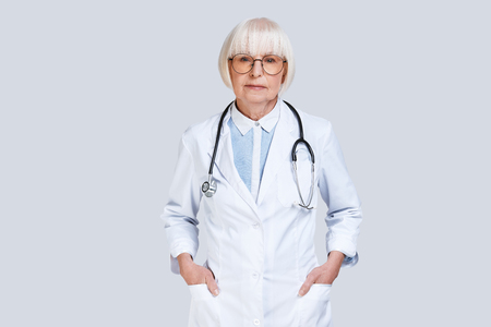 Reliable doctor. Beautiful senior woman in lab coat looking at camera while standing against grey background