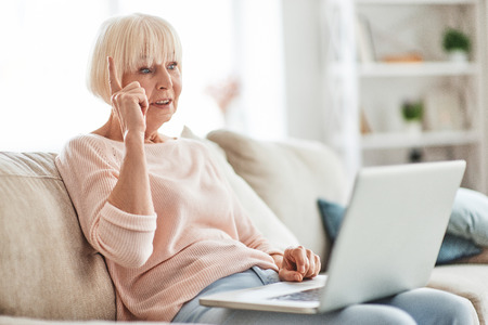 Fresh idea. Beautiful senior woman using laptop and gesturing while relaxing on the couch at home