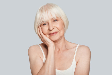 Time for yourself. Beautiful senior woman looking at camera and smiling while standing against grey background