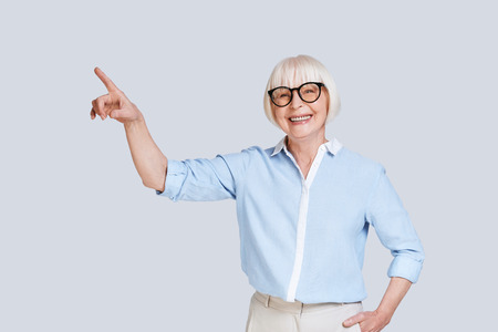 Look over there! Beautiful senior woman pointing copy space and smiling while standing against grey background