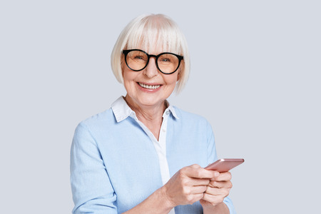 Sharing new ideas. Beautiful senior woman using her smart phone and smiling while standing against grey background Stock Photo