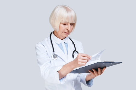 Taking care of paperwork. Beautiful senior woman in lab coat holding a clipboard with papers while standing against grey background