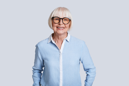 Mature expert. Beautiful senior woman looking at camera and smiling while standing against grey background Stock Photo
